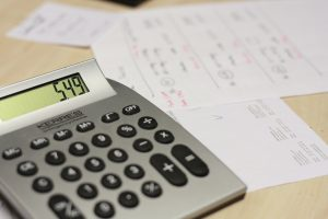 A calculator and some papers on a table.
