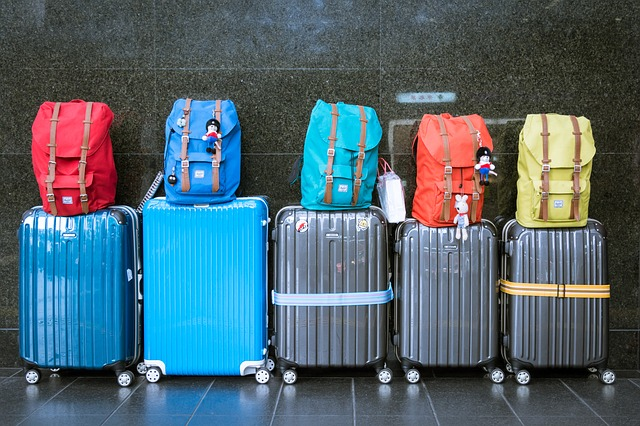 Five suitcases and bags lined against a wall.