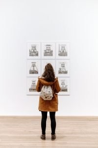 Woman in a museum inspecting a painting