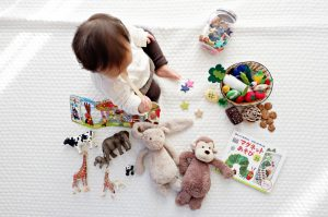 Toddler surrounded by toys - learn how to pack your child's room
