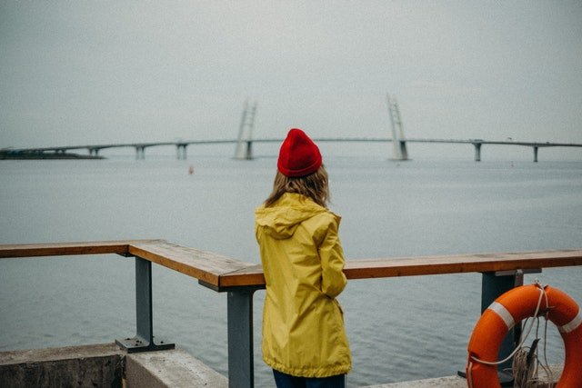 Woman in a yellow raincoat and a red hat standing next to the sea.