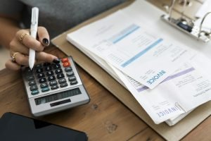 A woman calculating - defining a budget is a crucial step on your commercial relocation checklist