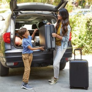 mother and son loading suitcases into a car
