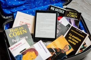 Books and a tablet in a suitcase - eco-friendly packing supplies
