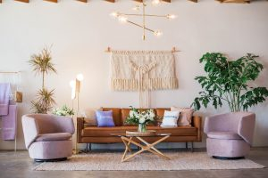 a leather sofa and two pink armchairs