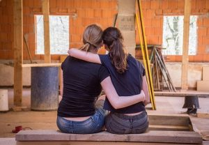 friends hugging - planning how to utilize wardrobe boxes after relocation