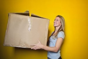 a girl carrying a large cardboard box
