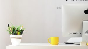 yellow ceramic mug beside iMac
