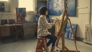 A girl painting a large painting