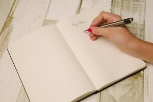 A hand writing down a plan in a notebook