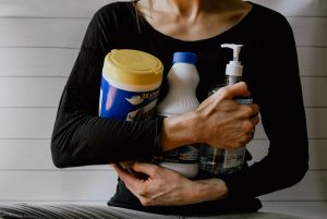 A woman holding cleaning supplies required to clean the house in a day