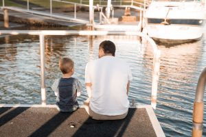 A father and the son sitting on the dock and talking