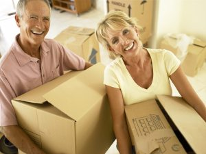 man and woman with boxes - pack your senior parents for moving