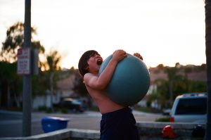 A frustrated kid holding a blue ball