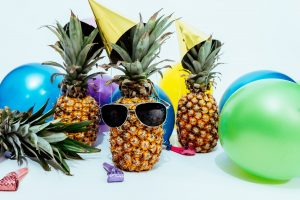 A pineapple with sunglasses and some baloons