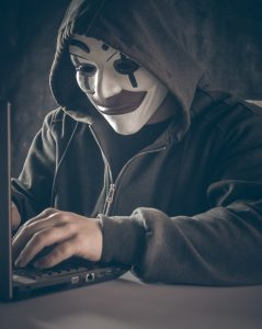 A man at a laptop, with a mask on