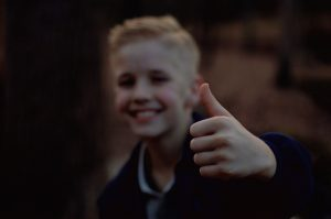 Young boy showing thumb up