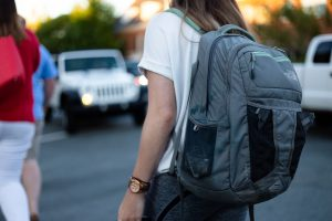 A girl with a grey backpack on her back