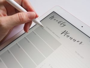 person writing on the white ipad