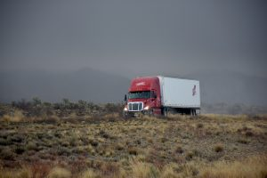 a red truck with a white trailer on the road