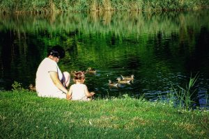 A woman sitting with a kid near a pond with some ducks