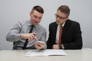 Two business men checking something on a mobile phone with a contract in front of them