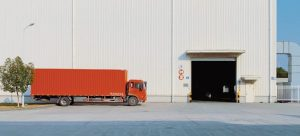 red moving truck parked by a white warehouse