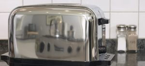 a gray toaster on the kitchen counter as one of many appliances that require professional handling