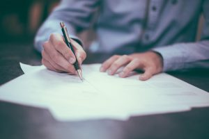 A man signing a moving contract