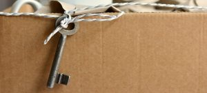 a cardboard box with a key chained to it