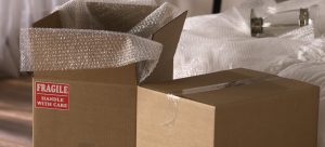 a pair of cardboard boxes with wrapping papers inside to help you speed up the packing process