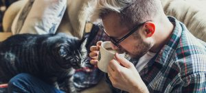 a man drinking a cup of coffee on the couch with his cat near him