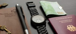 A passport, a watch, money, a planner, and a pen on a table.