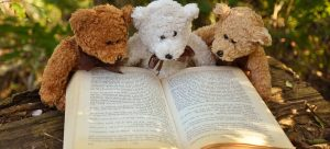 three different colours teddy bears pretending to read a book on packing a playroom in a day