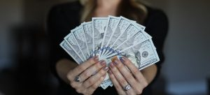 a woman holding dollar bills in her hands showing how to get back the money spent on relocation