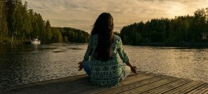 a woman sitting on a dock meditating
