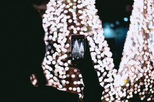 person taking photos of a christmas tree