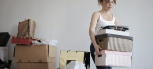 a woman taking boxes out of the room with a pile of items behind her