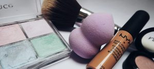 a make-up pallet next to a mascara, a brush and a beauty blender on the table before packing expensive cosmetics