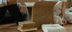 """a couple sitting on the floor next to a carboard box with a """"books"""" label"""