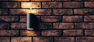 a black lamp on a red brick wall