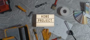 a sign saying home project with different painting tools around it as a way to remodel your bachelor room on a budget