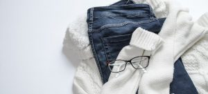 a pair of jeans atop of a while turtleneck and a pair of glasses