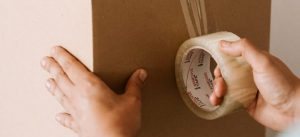 Man sealing a box with tape