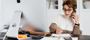 a woman sitting at the desk, talking on her phone and writing something down