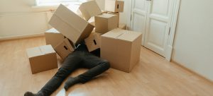a man laying on the floor with cardboard boxes atop of him
