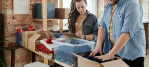 a man and a woman packing clothes into cardboard and plastic containers