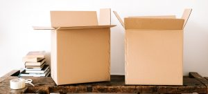a pair of cardboard boxes on the table with scissors and tape next to them