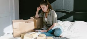 Girl with boxes sitting and looking at a tablet.