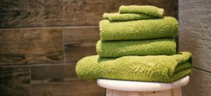 a stack of towels on a wooden chairs as something one could use to pack a fine china collection